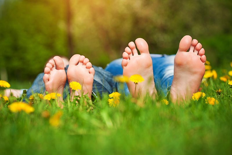 Photo of kid's feet, lying down in a field of grass.